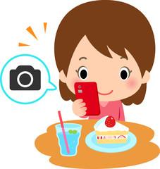 スマートフォンでケーキの写真を撮る女性