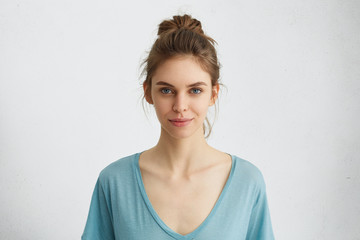 Portrait of beautiful female having blue shining eyes, thin lips, pure skin and dark hair tied in knot wearing blue loose blouse looking directly into camera having mysterious and glad expression
