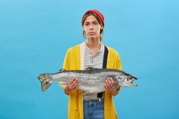 Young fisherwoman wearing red hat, yellow raincoat and jean overalls holding huge fish presenting her catch. Attractive woman buying big salmon or trout. Successful female angler posing with her catch
