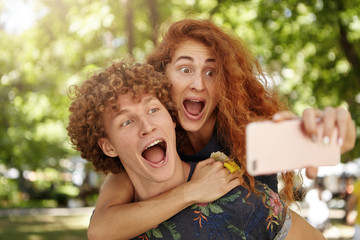 People, lifestyle, facial expressions concept. Shocked redhead female with curly hair riding on her husband back embracing him looking with bugged eyes and opened mouth at cell phone making selfie