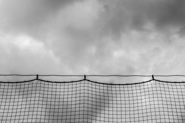 dark ominous storm clouds through netting at a baseball field