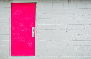 bright pink door in a gray cinder block building