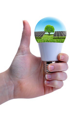 Hand with thumb up holding eco LED bulb with solar panel isolated on a white background. Energy saving lamp.