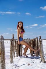 Beautiful girl on a salt lake in sun glasses
