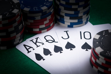 set of poker cards with the best combination for a player in the dark of a casino