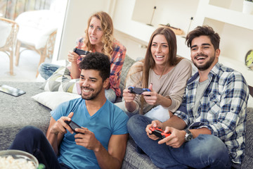 Friends  play video game with joystick at home
