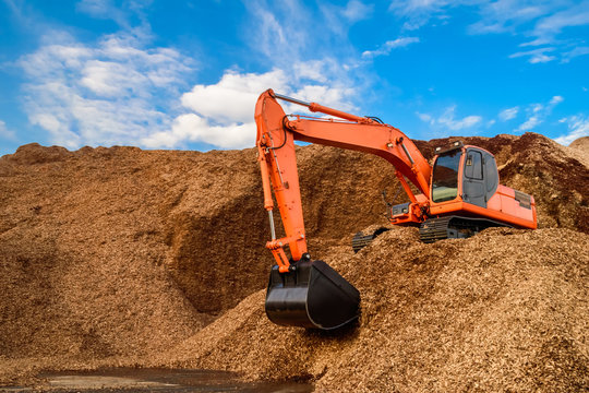 A load of wood chips handling by a powerful backhoe for loading onto trucks for exporting. Wood chips for paper production.