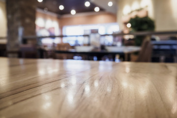 Empty wood table top with blurred cafe restaurant coffee shop interior background