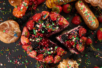 Bright and delicious fruit eclair and summer cake with currants, strawberries, blackberries, peaches on dark party background