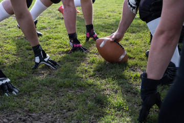 Hands of American football team prepared to serve the ball on grass.