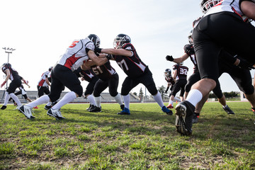 Two teams fighting while playing American football on stadium