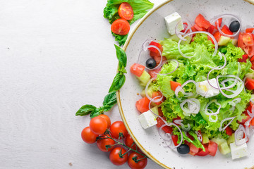 Greek salad of fresh vegetables and cheese. On a wooden background. Top view. Free space for your text.