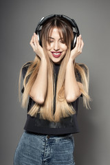 Awesome caucasian attractive sexy professional female model with long hair posing in studio wearing black shirt and wireless headphones, isolated on grey background