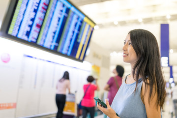 Woman checking flight number on board in airport
