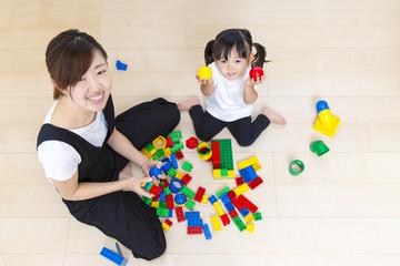 お母さんと玩具で遊ぶ幼い女の子の俯瞰