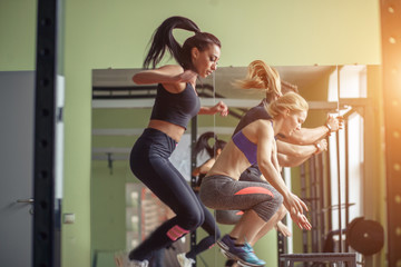 Group of athletic people jumpin over some boxes in a cross-training gym