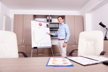 Young smiling businessman next to a flip chart in an office. Finance and business.