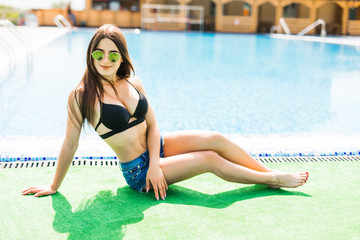 Woman sitting on the edge of swimming pool. Summer time