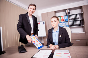 Businessman and businesswoman in office with charts on table. Corporate workers