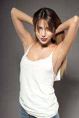 Awesome caucasian attractive sexy fashion model with extended hair posing in studio in white shirt, perfect make up, tanned skin, isolated on grey background, retouched image
