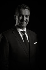 Portrait of adult confident businessman in studio photo on black background in black an white