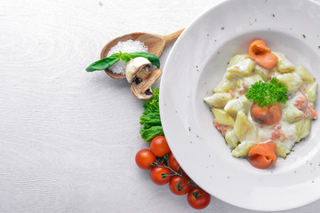 Potato dumplings with salmon and vegetables. On a wooden background. Top view. Free space for text.