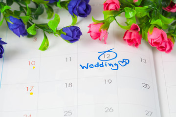 Wedding note on a calendar sets a reminder for the wedding day with flower..