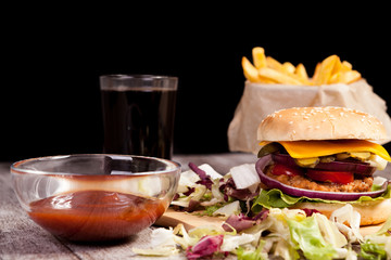 Burger on wooden plate next to fries on black background. Fast food. Unhealthy snack