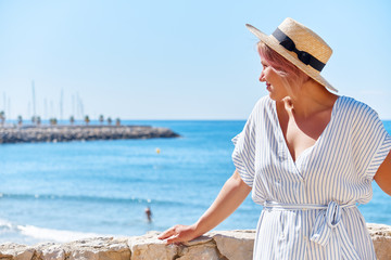 Beautiful girl in a summer dress and hat on the seashore near a background old city europe. Mediterranean Sea, Sitges, Spain