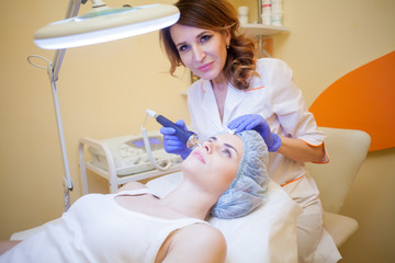 Cosmetology doctor makes facial procedures