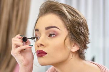 Woman using eyelash brush. Girl applying makeup. Date makeup ideas.