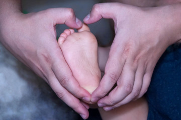 The foot of the baby in the father's hand