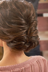 Braided female hairdo. Brown hair of a girl.