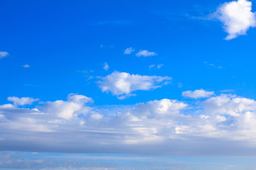 Blue sky background with white clouds on sunny summer or spring day.