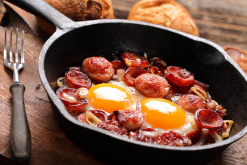Fried eggs with sausage and onion on frying pan