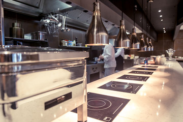 Professional kitchen , view counter in stainless steel . Bokeh .