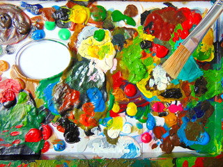 colorful dried paint on mixing palette with painting brush