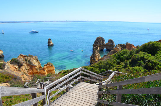 Wooden Stairs to Praia do Camilo at Algarve with blue Atlantic at Horizon