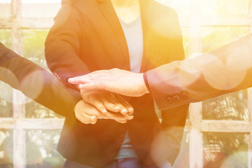 Warm tone of young Asian businessman suit joining united hand and business team touching hands together with flare light effect.