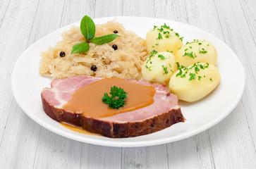 Kasselerbraten mit Sauerkraut und Salzkartoffeln - Tellergericht auf weißem Holzuntergrund