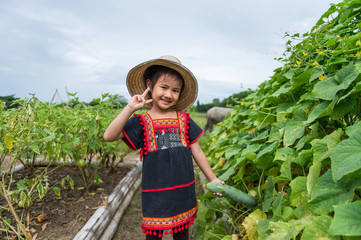 Little child (girl) take the vegetable in a organic garden