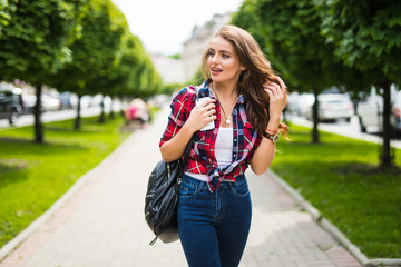 Summer sunny lifestyle fashion portrait of young stylish hipster woman walking on street with backpack