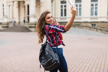 Young attractive playful tourist is making selfie on the phone outside wearing hat sunglasses