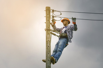 Electrician climbing poles, repairing power lines. Wall mural