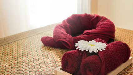 Red towels with white flower on the bed for spa, massage, therapy