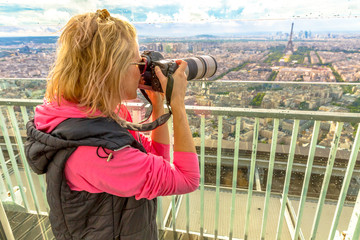 Travel woman photographer with telelens takes photos of Eiffel Tower from panoramic terrace of Tour Montparnasse. Female photographer in French capital, Europe.Paris skyline.Popular travel destination