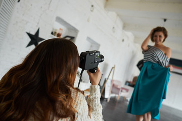 Backstage during photo shooting in studio: unrecognizable female photographer holding camera, taking pcitures of stunning beautiful young woman model who is posing in stylish clothing. Film effect