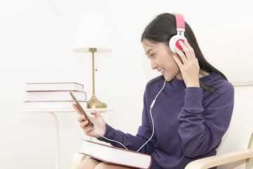 Young asian woman listen music from her phone with happyness..