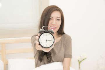 Young asian woman wake up in early morning and show clock on hand.