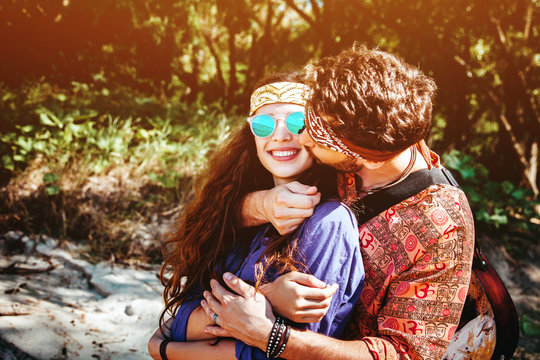 Beautiful young couple in love in hippie style with the guitar resting on the beach in summer. Man embracing his girlfriend and kisses